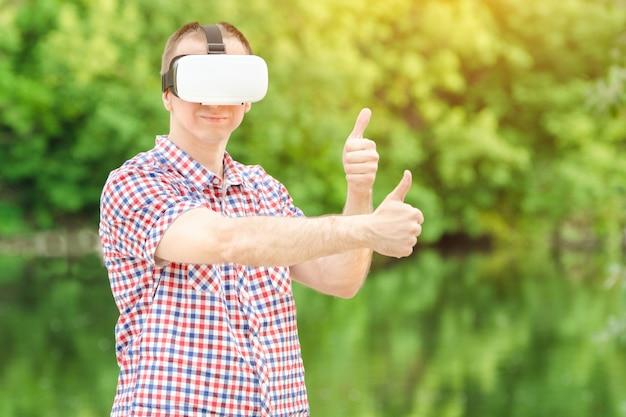 Homem em um capacete de realidade virtual no contexto da natureza.