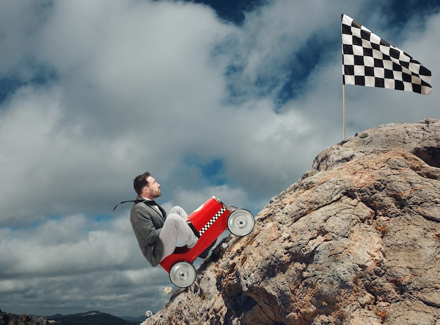 Homem em um carro de brinquedo dirigindo para uma bandeira de chegada