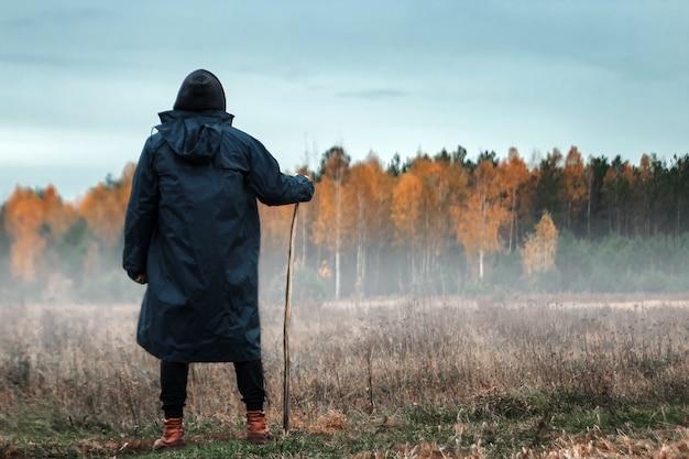 Homem em um casaco preto no nevoeiro