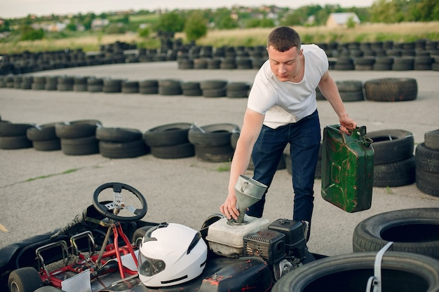 Homem em um circuito de kart com um carro