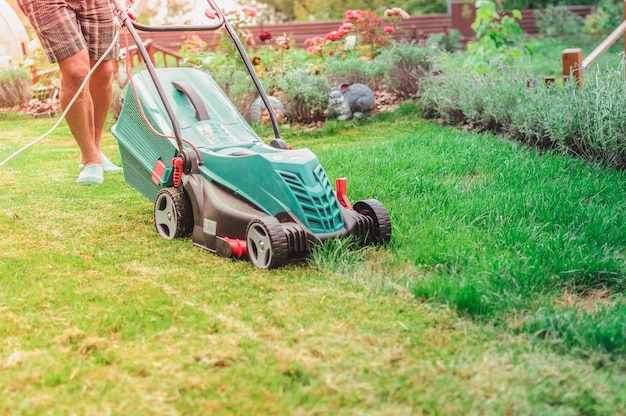 Homem em um dia ensolarado corta a grama no jardim