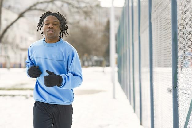 Homem em um parque de inverno. cara africano treinando lá fora. man run.