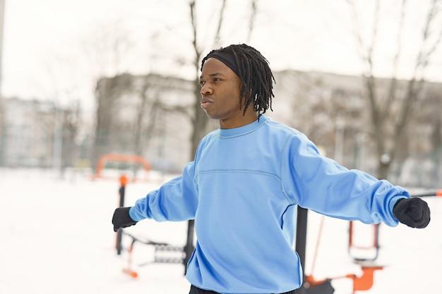 Homem em um parque de inverno. cara africano treinando lá fora.