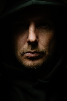 Homem em um quarto escuro com um capuz como um assassino. efeito artístico de grão e ruído.