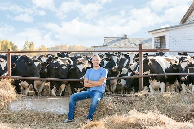 Homem em um rancho cercado por vacas