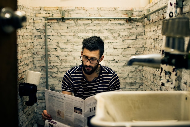 Homem, em, um, restroom, leitura, jornal