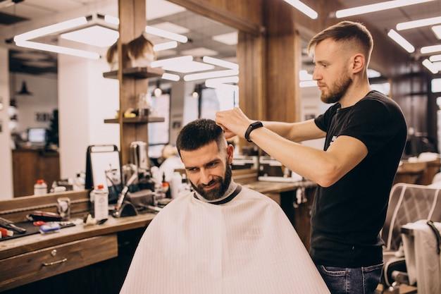 Homem em um salão de barbearia, fazendo o corte de cabelo e barba
