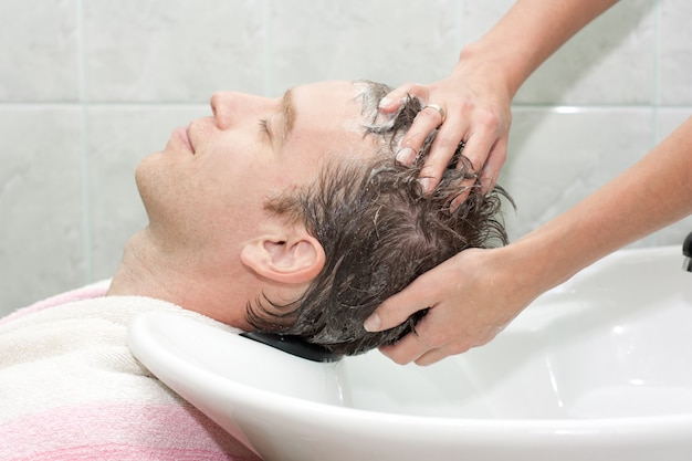 Homem em um salão de beleza lavando o cabelo