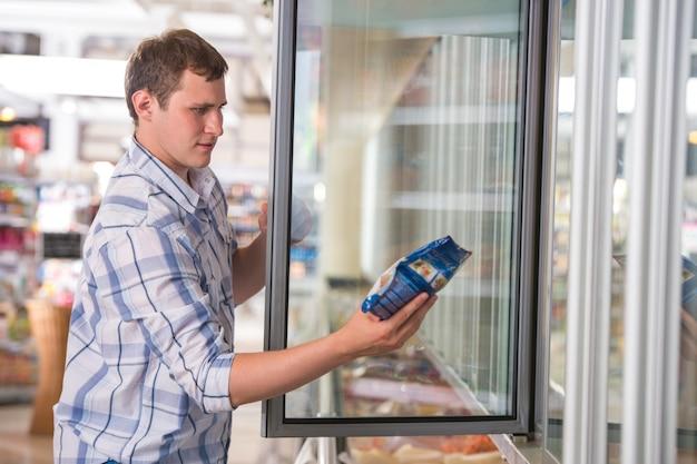 Homem em um supermercado em pé na frente do congelador