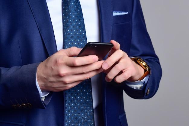 Homem em um terno azul escuro verifica as mensagens em seu telefone.