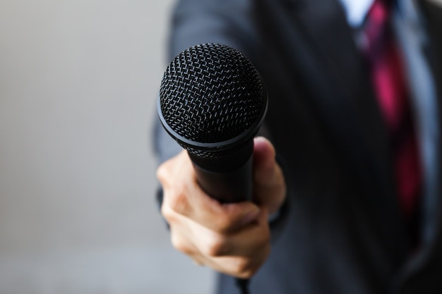 Homem em um terno de negócio segurando um microfone, indicando eventos formais de negócios
