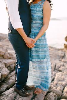 Homem em um terno e mulher em um vestido longo com um enfeite estão em uma margem de pedra de mãos dadas