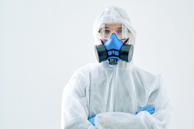 Homem em um traje anti-risco, um respirador e uma máscara protetora. foto com uma cópia-espaço.