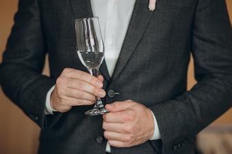 Homem em uma camisa branca com uma taça de champanhe mostra