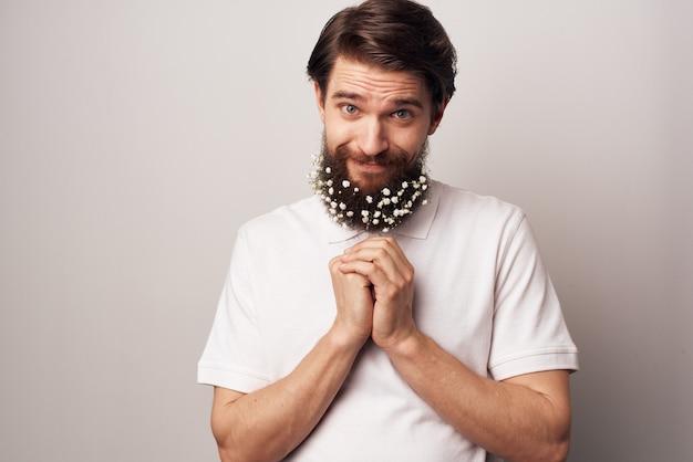 Homem em uma camisa branca e pode flores em um fundo claro de decoração de barba. foto de alta qualidade