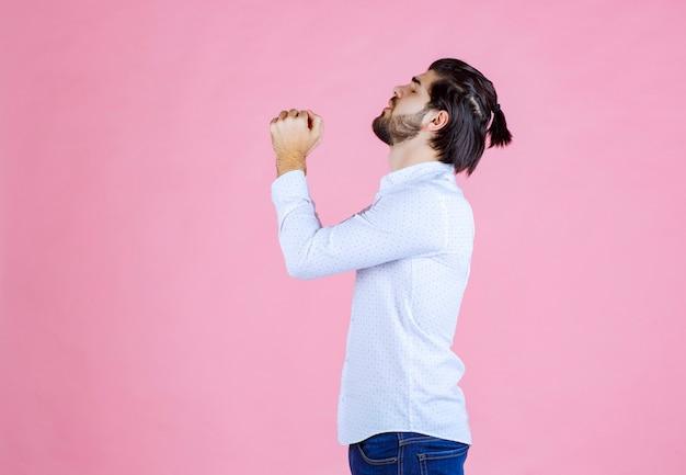 Homem em uma camisa branca, unindo as mãos e orando.