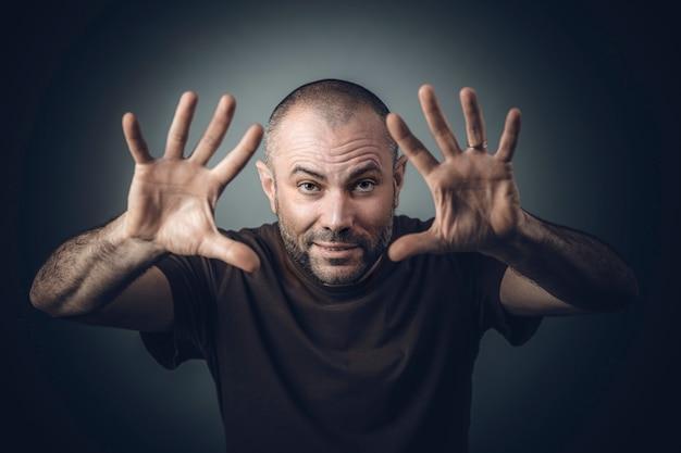 Homem em uma camisa com a posição da mão aberta, como se estivesse realizando mágica.