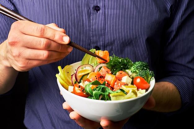 Homem em uma camisa detém picar tigela com salmão, abacate, queijo e chuha com pauzinhos