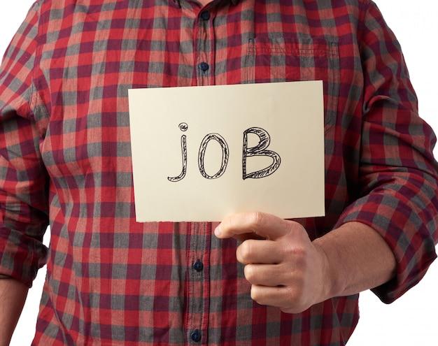 Homem em uma camisa xadrez e calça jeans mantém um pedaço de papel com o trabalho de inscrição