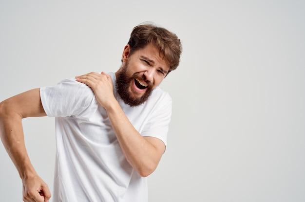 Homem em uma camiseta branca estresse remédio dor no pescoço luz de fundo