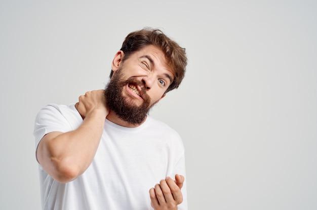 Homem em uma camiseta branca estresse remédio para dor no pescoço isolado fundo