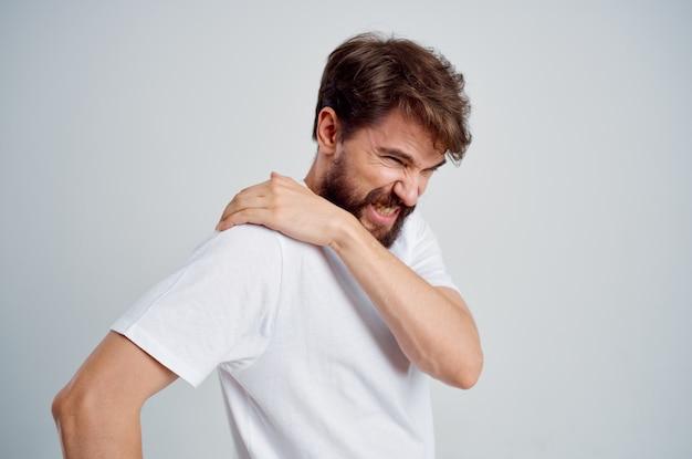 Homem em uma camiseta branca estresse remédio para dor no pescoço tratamento de estúdio