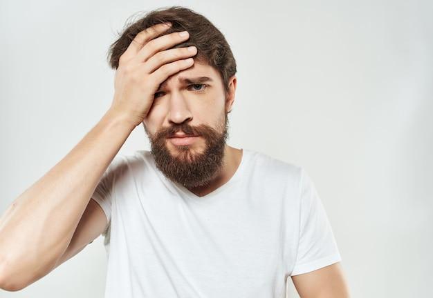 Homem em uma camiseta branca expressivo olhar descontentamento estilo de vida. foto de alta qualidade