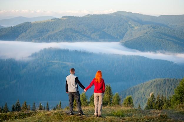 Homem em uma colina, desfrutando de uma manhã de neblina sobre as montanhas poderosas