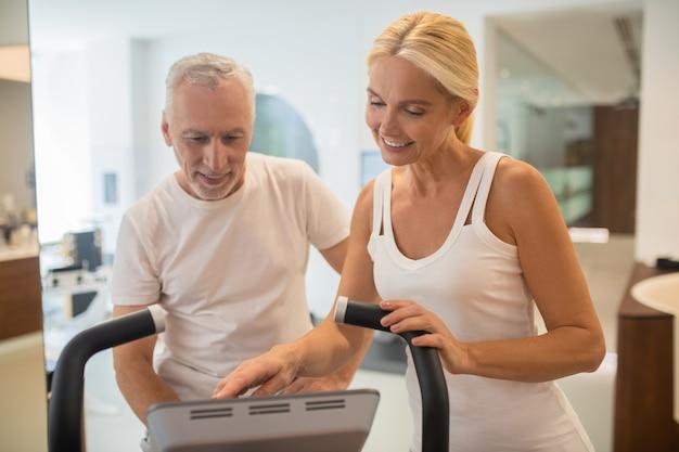 Homem em uma esteira e instrutora olhando enquanto liga a máquina de ginástica