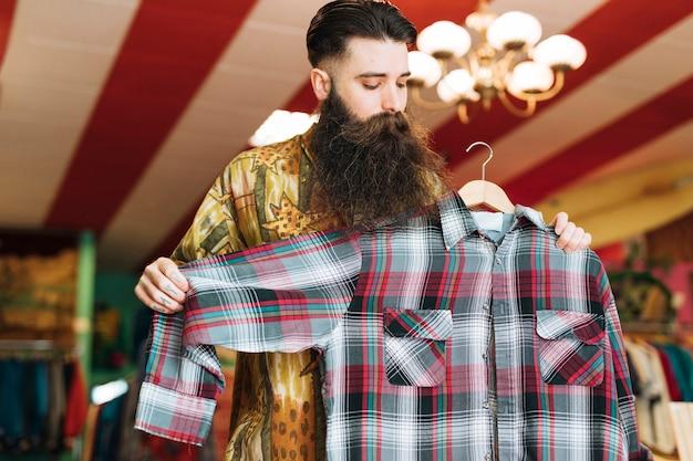 Homem em uma loja elegante, verificando a camisa xadrez