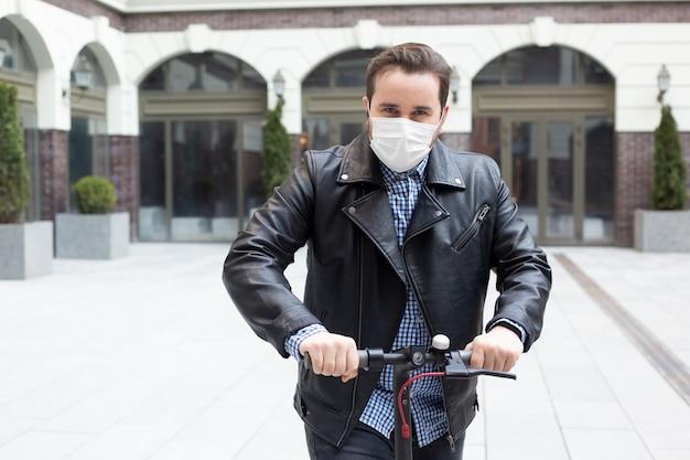Homem em uma máscara cirúrgica em um fundo de um edifício moderno em scooter elétrico, coronavírus, doença, infecção, quarentena, máscara médica
