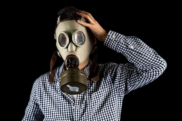 Homem em uma máscara de gás em um fundo preto. copie o espaço