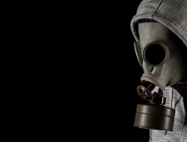 Homem em uma máscara de gás em um fundo preto. proteção contra vírus