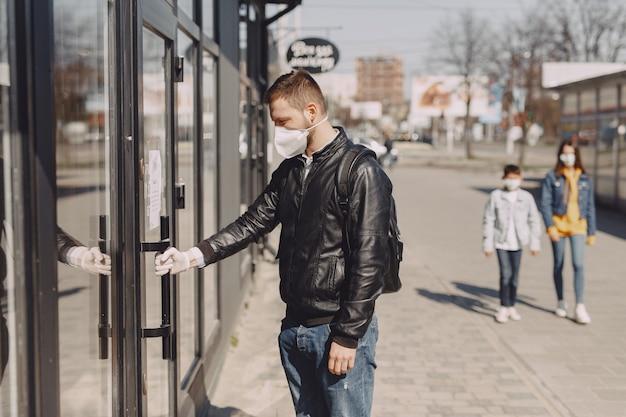 Homem em uma máscara de pé na rua