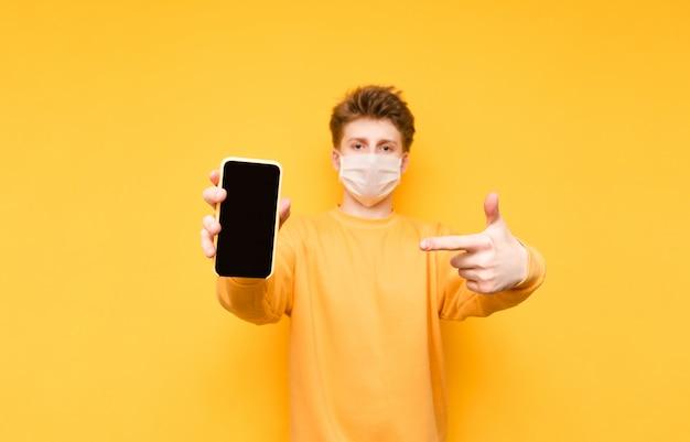 Homem em uma máscara de proteção médica isolada em um amarelo, mantém um smartphone com uma tela preta e aponta um dedo. pandemia do coronavírus.