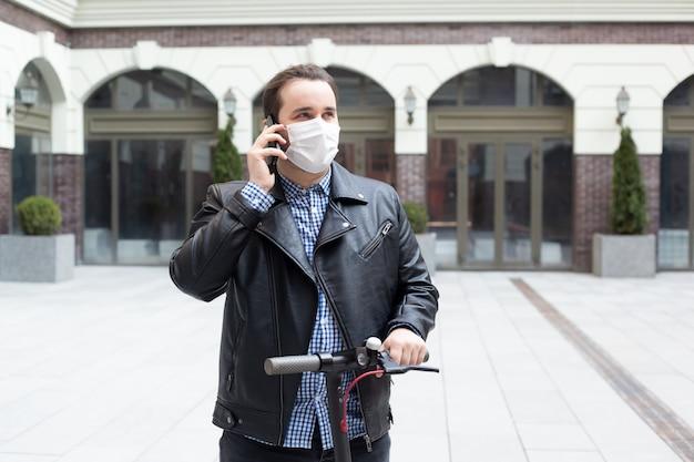 Homem em uma máscara médica em um fundo de um edifício moderno em scooter elétrico, coronavírus, doença, infecção, quarentena, máscara médica