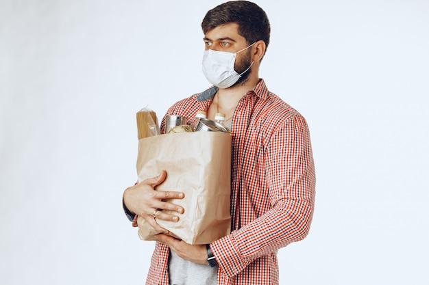Homem em uma máscara médica protetora com um saco de uma mercearia. entrega de alimentos