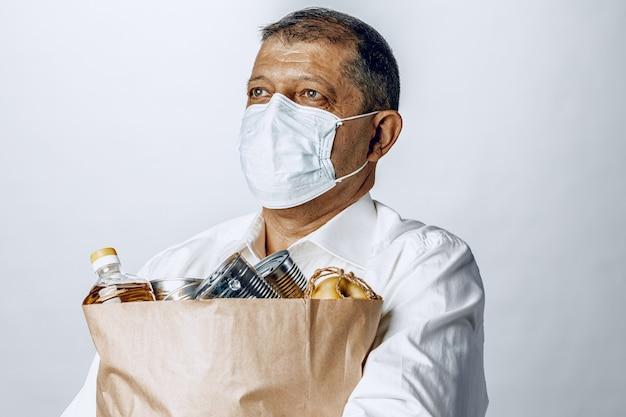 Homem em uma máscara médica protetora com uma sacola de uma mercearia