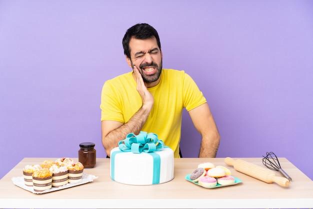 Homem em uma mesa com um bolo grande com dor de dente