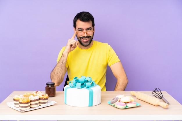 Homem em uma mesa com um bolo grande com óculos e feliz