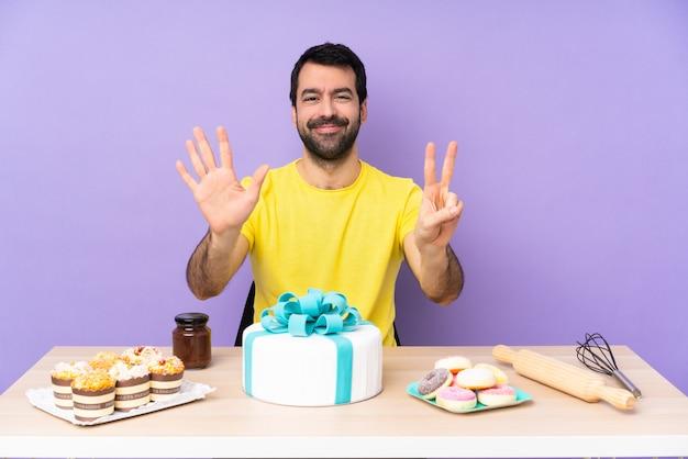 Homem em uma mesa com um bolo grande, contando sete com os dedos