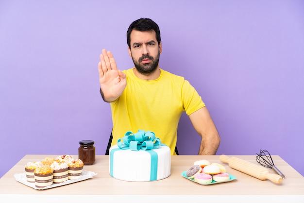 Homem em uma mesa com um bolo grande, fazendo o gesto de parada