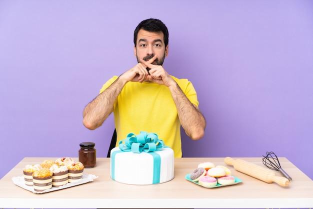 Homem em uma mesa com um bolo grande, mostrando um sinal de gesto de silêncio