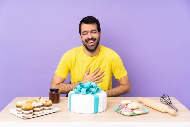 Homem em uma mesa com um bolo grande, sorrindo muito
