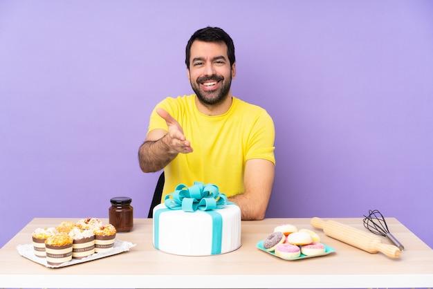 Homem em uma mesa com um grande bolo apertando as mãos para fechar um bom negócio