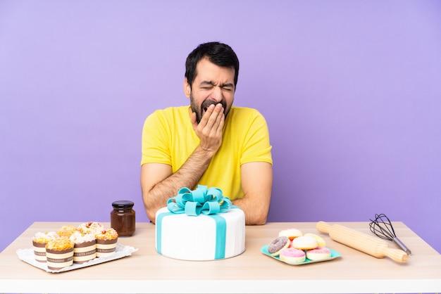 Homem em uma mesa com um grande bolo bocejando