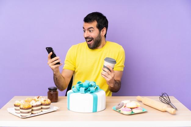 Homem em uma mesa com um grande bolo segurando café para levar e um celular