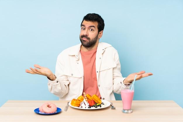 Homem em uma mesa tomando waffles de café da manhã e um milk-shake com dúvidas ao levantar as mãos