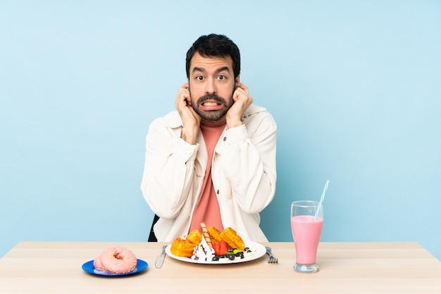 Homem em uma mesa tomando waffles de café da manhã e um milk-shake frustrado e cobrindo as orelhas