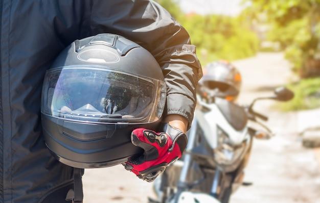 Homem em uma motocicleta com capacete e luvas é roupas de proteção para o motociclismo